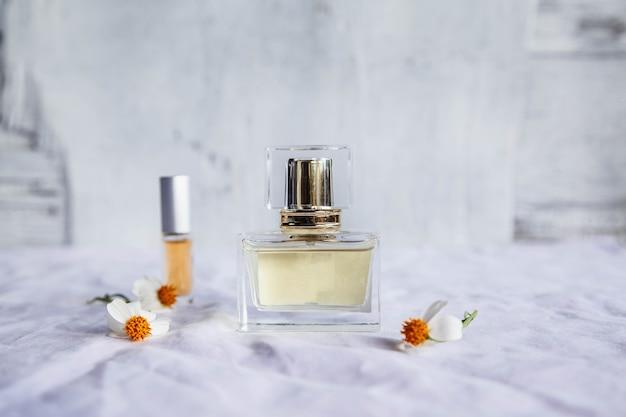 Parfum doré et flacons de parfum sur surface blanche