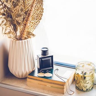Parfum féminin et bijoux en or posés sur une pile de livres sur le rebord de la fenêtre. décor à la maison en couleur dorée