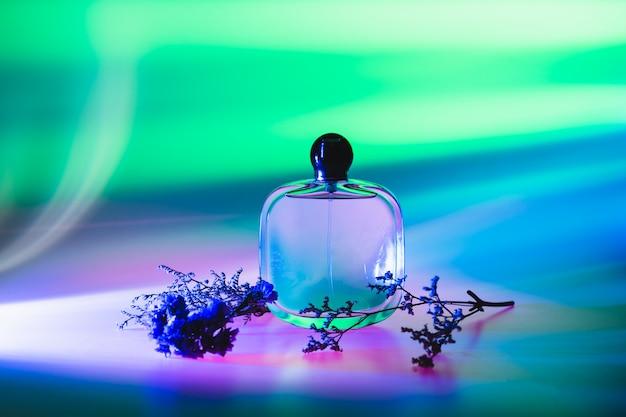 Parfum féminin coloré abstrait dans la bouteille avec bouquet de fleurs séchées. publicité de produits de parfum. résumé nature morte.