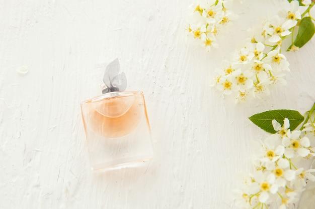 Parfum féminin dans une belle bouteille et fleurs de cerisier sur fond blanc. outils et accessoires à plat pour femme