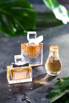 Parfum de femme dans une belle bouteille avec des feuilles vertes sur un béton noir avec la lumière du soleil