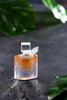 Parfum de femme dans une belle bouteille avec des feuilles vertes