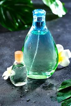Parfum de femme dans une belle bouteille avec des fleurs et des feuilles sur un béton noir avec la lumière du soleil