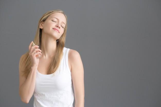 Parfum de femme. portrait féminin avec parfum en spray.