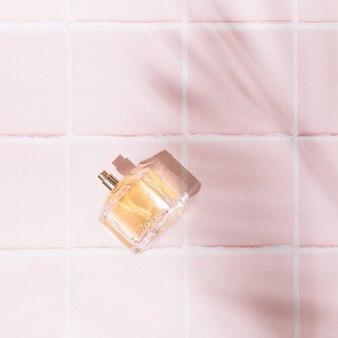 Parfum golder dans l'eau sur fond rose pastel doux avec des tuiles. produits de beauté féminins de luxe. style minimaliste. ombre de feuille de palmier d'été.