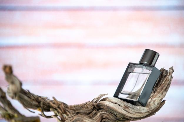 Parfum homme vue de face sur une branche d'arbre séchée isolée sur fond nu avec espace libre