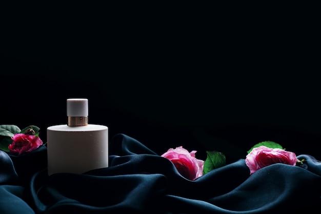 Parfum pour femme avec des fleurs sur fond noir