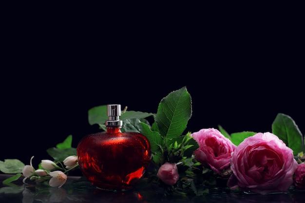 Parfum rouge et roses sur fond sombre