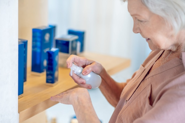 Parfumerie. femme aux cheveux gris testant des parfums dans un institut de beauté