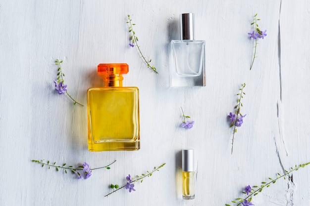 Parfums et flacons de parfum sur un fond en bois blanc