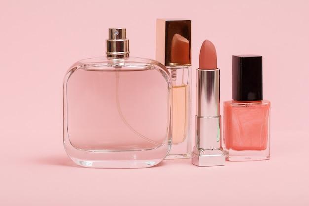 Parfums pour femmes, rouge à lèvres et flacon avec vernis à ongles sur fond rose. cosmétiques et parfums pour femmes.