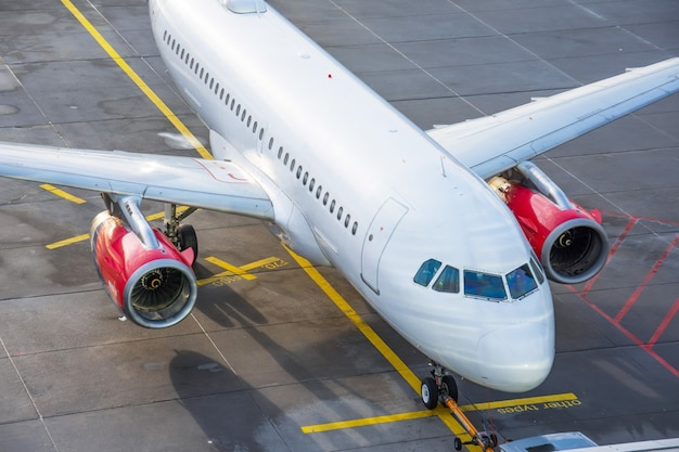 Parking d'avion commercial à l'aéroport ensoleillé, vue de dessus.