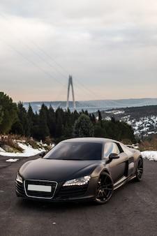 Un parking coupé sport noir de luxe sur la route.