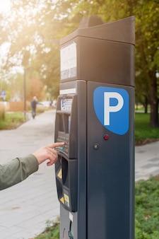 Parking dans la rue de la ville. terminal pour parking payant. la main de l'homme appuie sur le bouton.