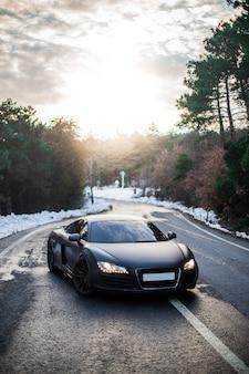 Parking de luxe coupé sport noir avec lumières allumées dans la forêt.