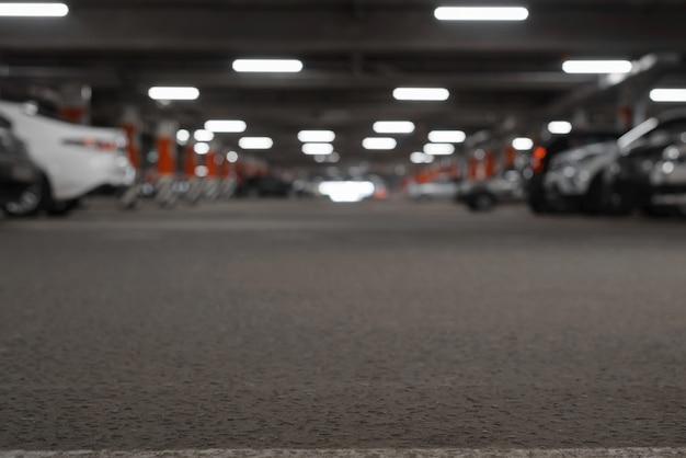 Parking souterrain arrière-plan défocalisé, low angle view. les voitures garées et les lumières sont floues, mise au point sélective sur le sol. espace de copie