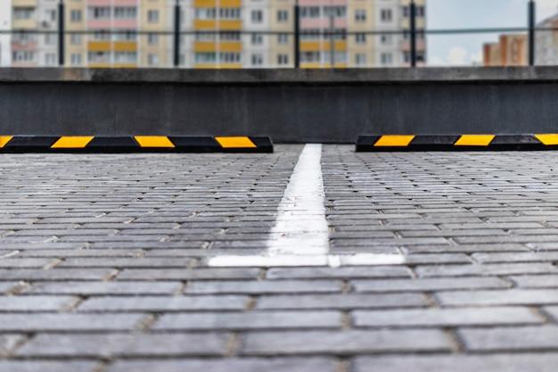 Un parking vide dans un quartier résidentiel avec des arrêts de stationnement jaunes pour les voitures. fermer. arrêtez le limiteur de stationnement.