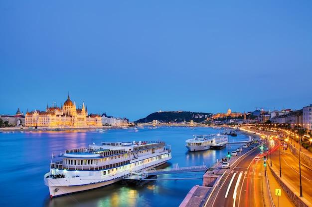 Parlement et bord de la rivière à budapest en hongrie avec des bateaux de tourisme pendant le coucher du soleil heure bleue