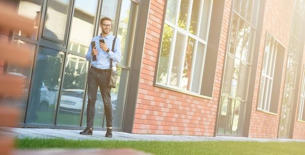 Parler d'affaires jeune homme d'affaires caucasien confiant portant une chemise bleue et des lunettes tenant son
