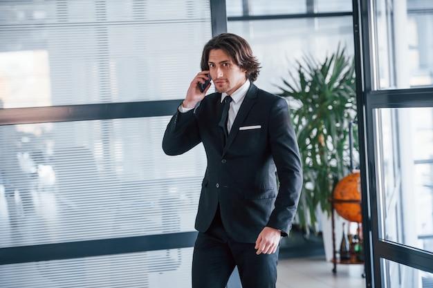 Parler au téléphone au bureau. portrait de beau jeune homme d'affaires en costume noir et cravate.