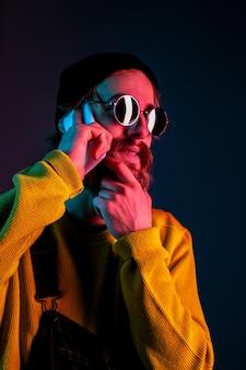 Parler au téléphone dans des lunettes de soleil. portrait de l'homme caucasien sur l'espace dégradé en néon