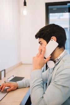 Parler au téléphone mâle travaillant à l'ordinateur portable