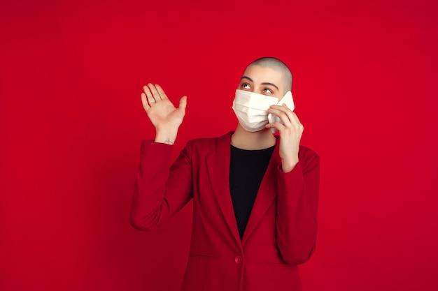 Parler au téléphone. portrait de jeune femme chauve caucasienne isolée sur mur rouge. beau modèle féminin en gants, masque facial. émotions humaines, expression faciale, ventes, concept publicitaire.