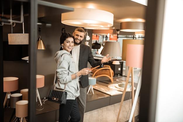 Parler des avantages. dame souriante positive appréciant le processus d'achat dans la section éclair lors de la visite d'un magasin de meubles