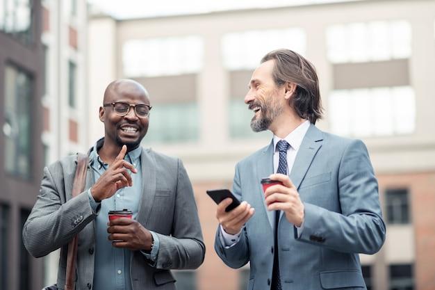 Parler à un collègue. homme d'affaires aux cheveux gris tenant un smartphone parlant à un collègue buvant du café