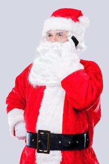 Parler avec les elfes. père noël traditionnel parlant au téléphone portable en se tenant debout sur fond gris