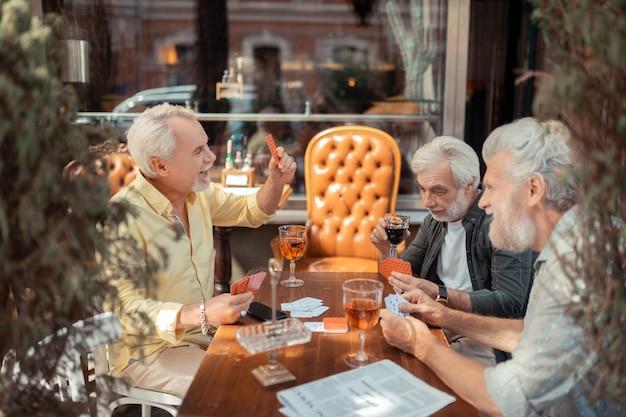 Parler et jouer. hommes retraités parlant et jouant le soir le week-end
