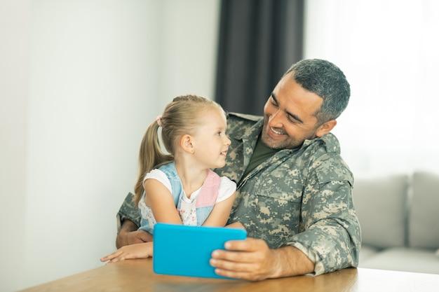 Parler à papa. jolie fille blonde parlant à papa qui rentre à la maison après son service militaire