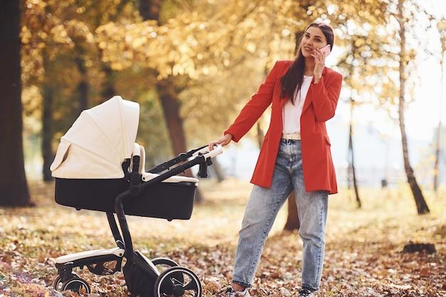 Parler par téléphone. une mère en manteau rouge se promène avec son enfant dans le landau du parc à l'automne.