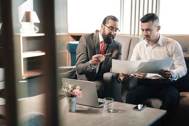Parlez à l'investisseur. jeune homme d'affaires prometteur parlant à son investisseur barbu portant des lunettes