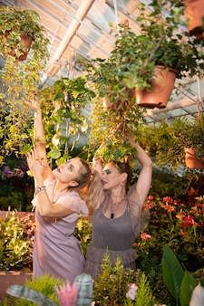 Parmi les fleurs. belles belles femmes debout dans la serre en posant