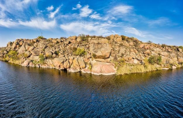 Parmi les gros rochers, un ruisseau lisse et brillant coule dans la lumière chaude du soir dans la pittoresque ukraine.