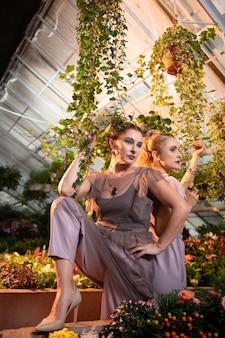 Parmi les plantes. belles femmes attirantes touchant une plante verte en se tenant sous le pot de fleurs