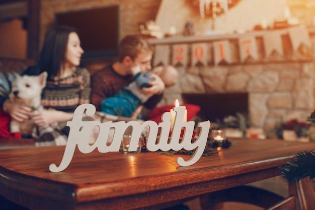Parole «famille» avec une famille assis sur le canapé en arrière-plan sur noël