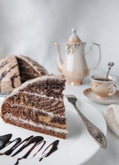 Une part de gâteau marbré à la crème. garni de glaçage et de chocolat. sur une assiette blanche avec une fourchette. le fond est gris. en arrière-plan, une cafetière, une tasse et un gâteau. l'arrière-plan est flou.