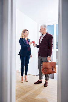 Partage de la carte de visite. homme d'affaires prospère portant des chaussures en cuir marron élégant donnant sa carte de visite son jeune partenaire attrayant