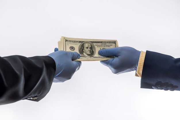 Partage de dollars entre deux hommes d'affaires pour payer des marchandises dans des gants médicaux, isolés sur fond blanc. période pandémique de coronavirus