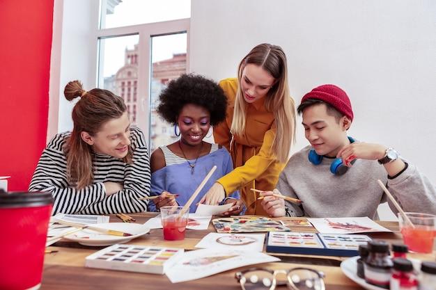 Partage d'expérience. artiste célèbre talentueuse aux cheveux blonds partageant son expérience avec de jeunes étudiants