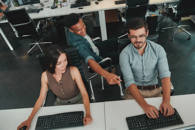 Partage d'idées fraîches vue de dessus de jeunes gens d'affaires travaillant sur des ordinateurs et parlant avec