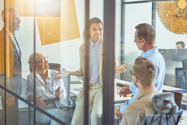 Partage d'idées nouvelles jeune employée de bureau métisse discutant de quelque chose avec des collègues
