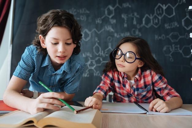 Partage d'idées. participation d'élèves curieux et habiles assis à l'école et bénéficiant d'un cours d'anglais tout en prenant des notes et en apprenant de nouveaux mots