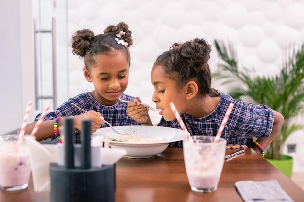 Partage de pâtes. sœurs à la mode aux cheveux noirs bouclés partageant une grande assiette avec des pâtes tout en étant assis au restaurant