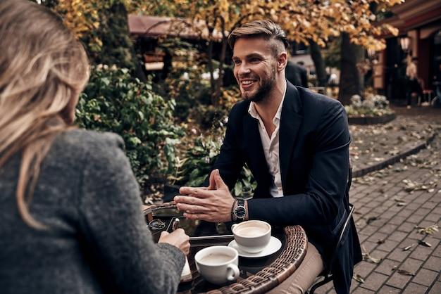 Partager de bonnes idées. beau jeune homme en vêtements décontractés intelligents souriant tout en discutant avec une jeune femme au restaurant en plein air