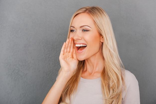 Partager de bonnes nouvelles. cheerful young blonde woman holding hand près de sa bouche et à l'écart