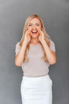 Partager de bonnes nouvelles. heureuse jeune femme aux cheveux blonds se tenant la main près de sa bouche et
