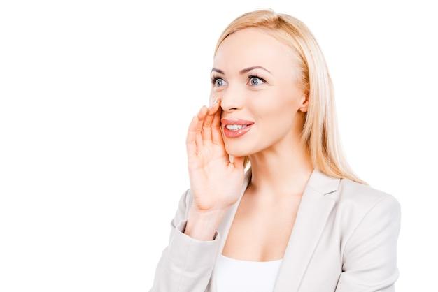 Partager de bonnes nouvelles. joyeuse femme d'affaires mature tenant la main près de sa bouche et regardant ailleurs en se tenant debout sur fond blanc